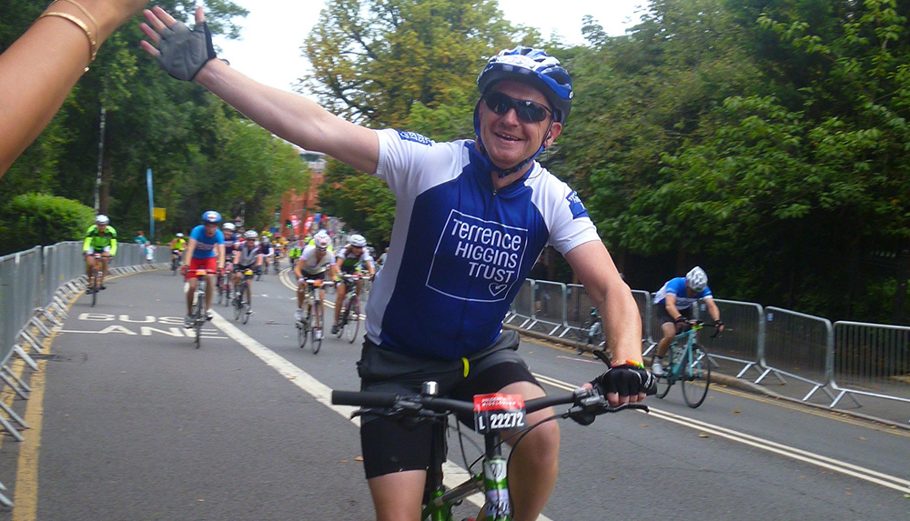 Cyclist waving in Prudential London-Surrey 100