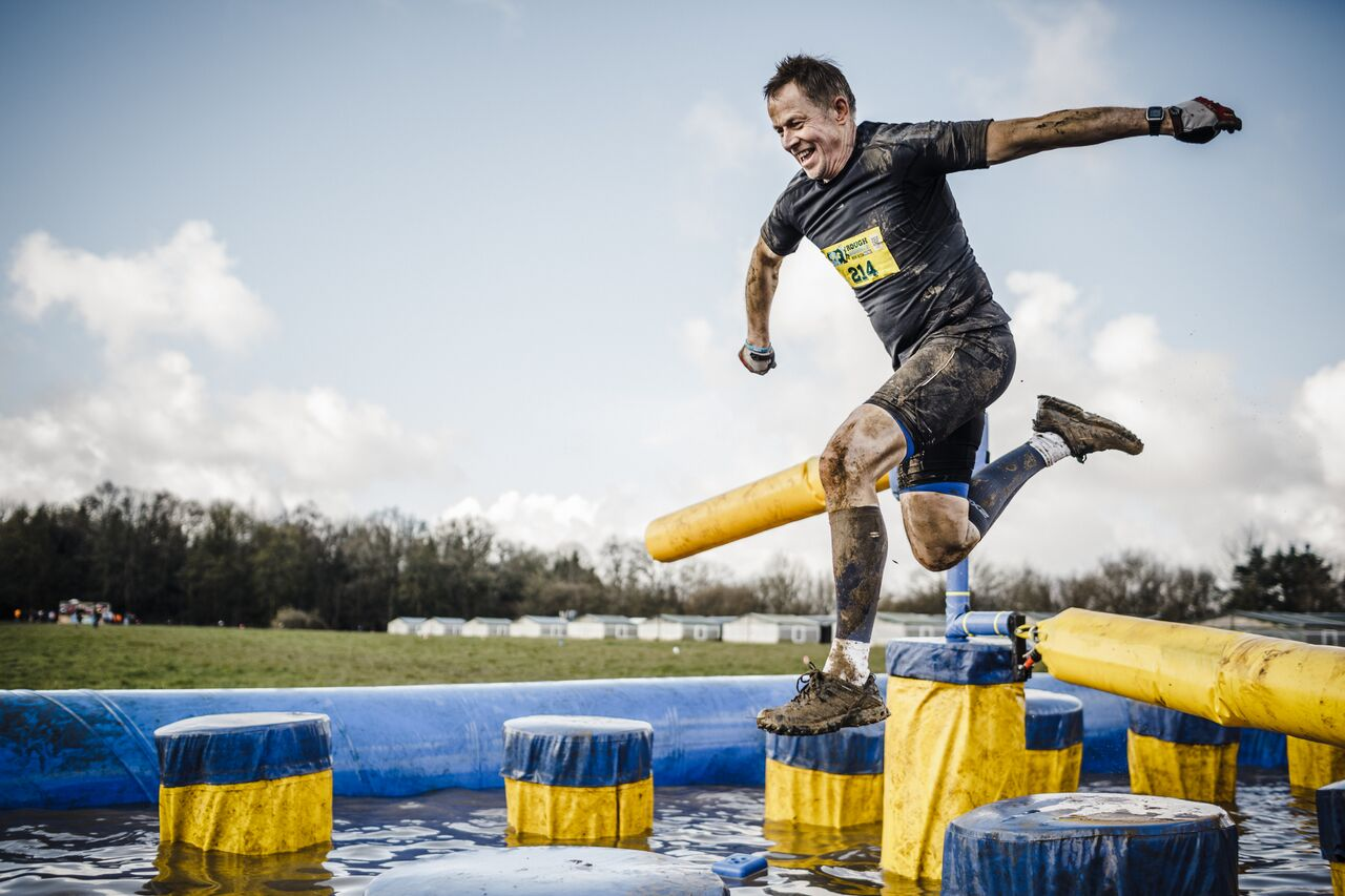 Rough Runner man leaping over water obstacle