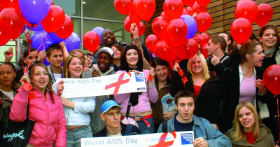 Students holding World AIDS Day banners and balloons