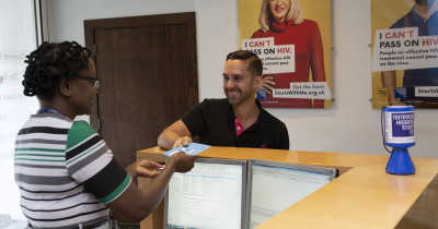 Man being given a leaflet in at a Terrence Higgins Trust reception desk