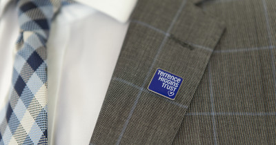 Terrence Higgins Trust lapel pin on a suit jacket