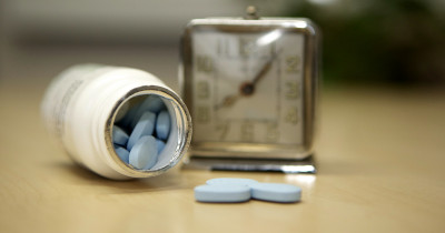 Blue pills next to an alarm clock