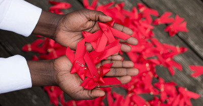 World AIDS day red ribbons in hands