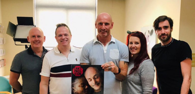 Gareth Thomas holding Can't Pass It On poster with THT staff