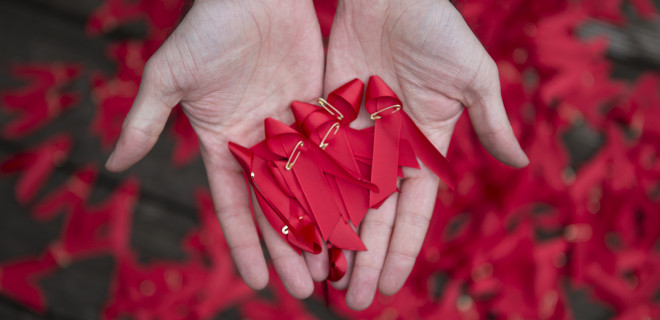 A hand holding red ribbons