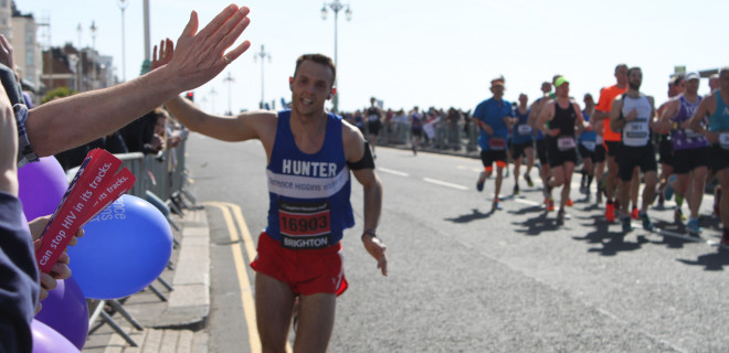 Marathon runner high-fiving crowd in Brighton