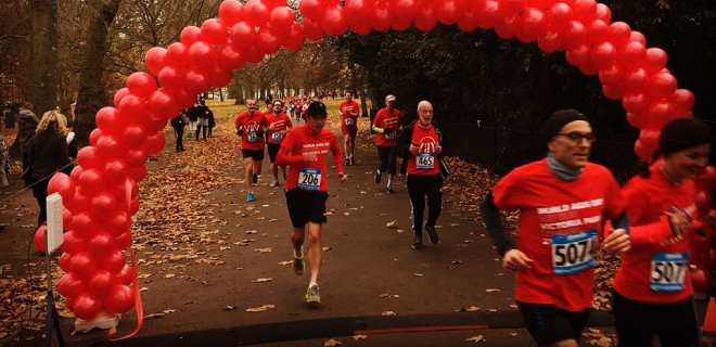 Red Run runners in Victoria Park, running through balloon archway