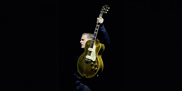 Bryan Adams holding up guitar