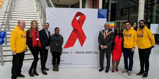 People standing either side of a red ribbon sign in an office building