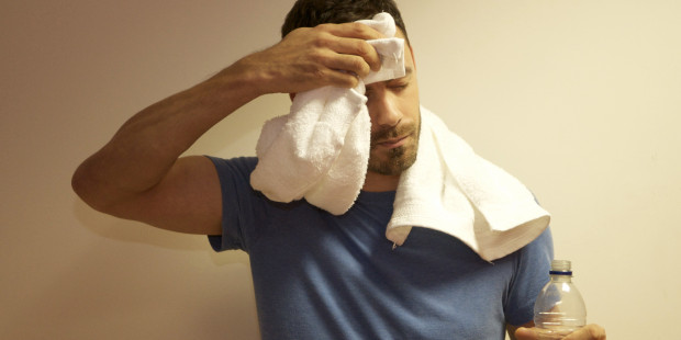 Man with towel and water after exercise